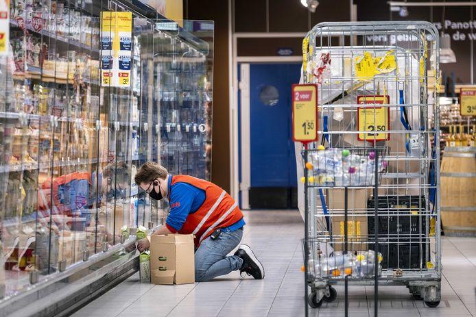 Een medewerker vult de schappen in supermarkt.