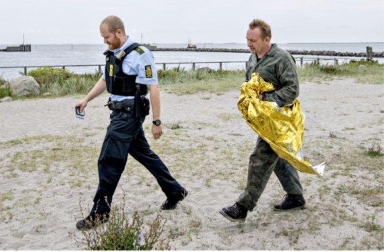 Peter Madsen werd door vissers opgepikt en afgezet nadat zijn duikboot was gezonken. Aan land stonden journalisten en politiemensen te wachten.   Beeld