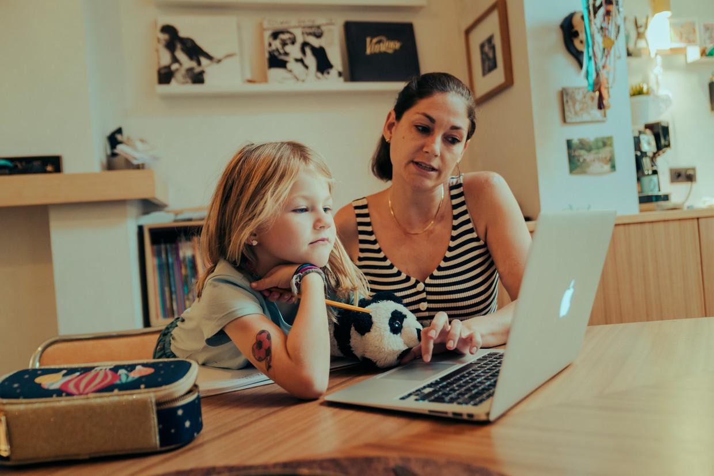 Kaat De Man helpt haar dochter Mary-Lou (6) met afstandsonderwijs. Het hele eerste leerjaar van haar school zit in quarantaine thuis. Beeld Jef Boes