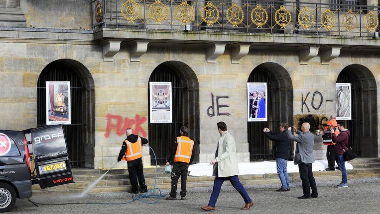 Medewerkers van de gemeente zijn bezig de woorden ' Fuck de Koning' van de muren van het Paleis op de Dam te verwijderen. Beeld anp