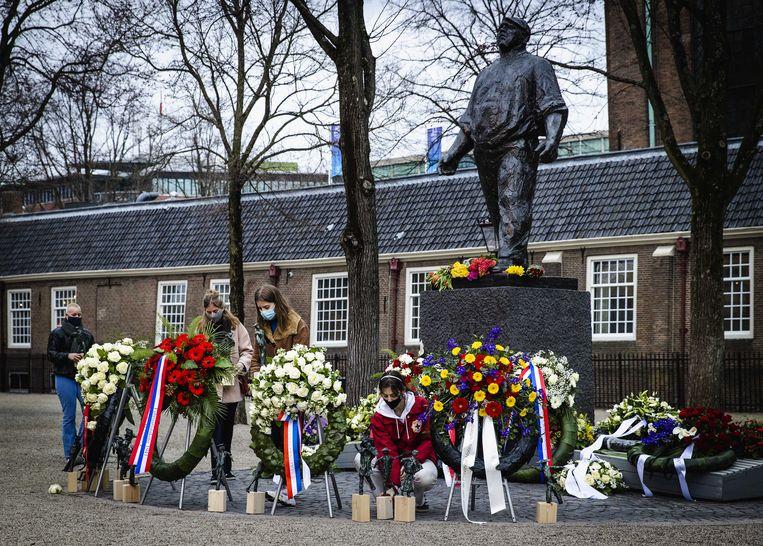 Scholieren van  de Rosa Boekdrukkerschool leggen bloemen bij de Dokwerker tijdens de herdenking van de Februaristaking.  Beeld ANP
