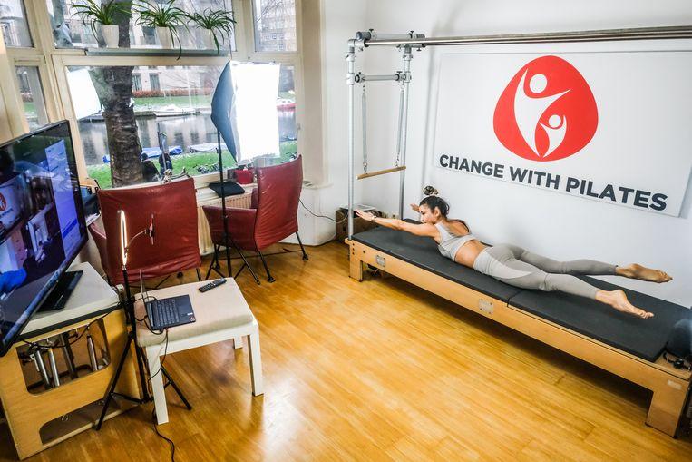Pilates-docent Deniz Ertas van Gennip geeft online-les vanuit huis. Beeld Joris van Gennip