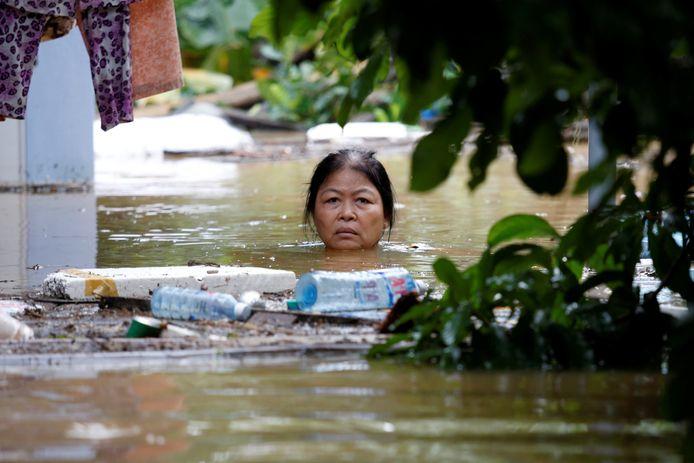 Een vrouw waadt door de ondergelopen straten van de Vietnamese kuststad Hôi an, die hevig is getroffen door tyfoon Damrey.  Foto Kham