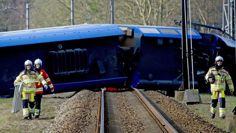 Hulpdiensten bij een passagierstrein die bij Dalfsen tegen een hoogwerker gebotst is. Enkele treinstellen zijn op hun kant komen te liggen. Beeld ANP