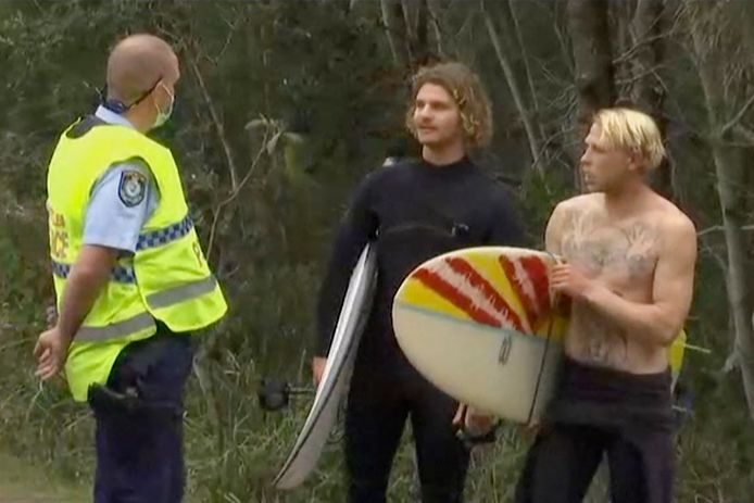 Een agent praat met twee surfers bij Emerald beach in Coffs Harbour in Australië, nadat een andere surfer overleed aan zijn verwondingen toegebracht door een haai.