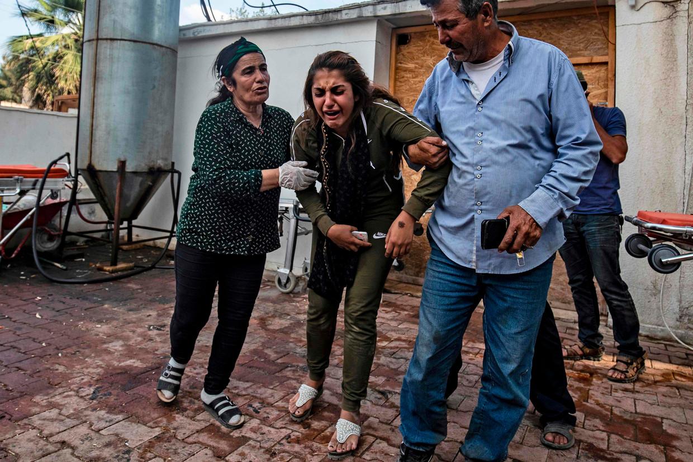 Een vrouw reageert op het lichaam van een man gedood door Turks artillerievuur, die net arriveert bij een ziekenhuis in de buurt van Tal Tamr, kort na het staakt-het-vuren. Beeld AFP