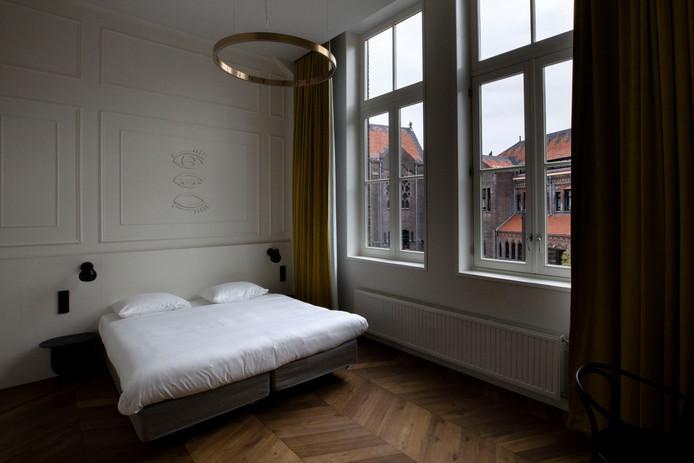 Een van de 80 hotelkamers in de lange gangen van DOMUSDELA. Hier is ook een muur van de oorspronkelijke kerk uit 1420 terug te zien.