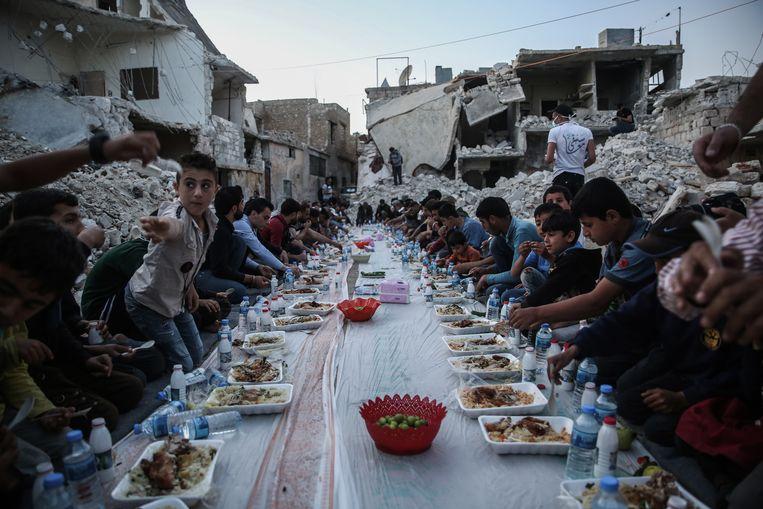 Bewoners van een verwoeste buurt in Al Atarib eten een maaltijd. Sancties maken het voor hulporganisaties bijna onmogelijk nog vluchtelingen in Syrië te helpen. Beeld Anas Alkharboutli / ANP