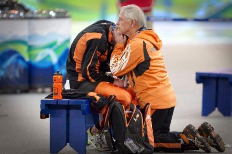Een aangeslagen Sven Kramer wordt na zijn diskwalificatie getroost door chef de mission Henk Gemser ANP Beeld