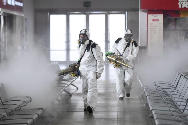 Vrijwilligers desinfecteren het treinstation van Changsha in China.  Beeld Photo News