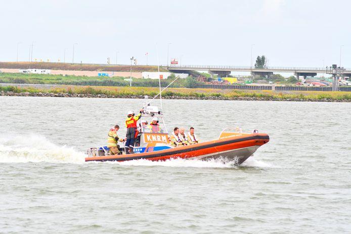 De reddingsboot van KNRM haalt mensen op die op het IJsselmeer vast op een brandend schip zitten.