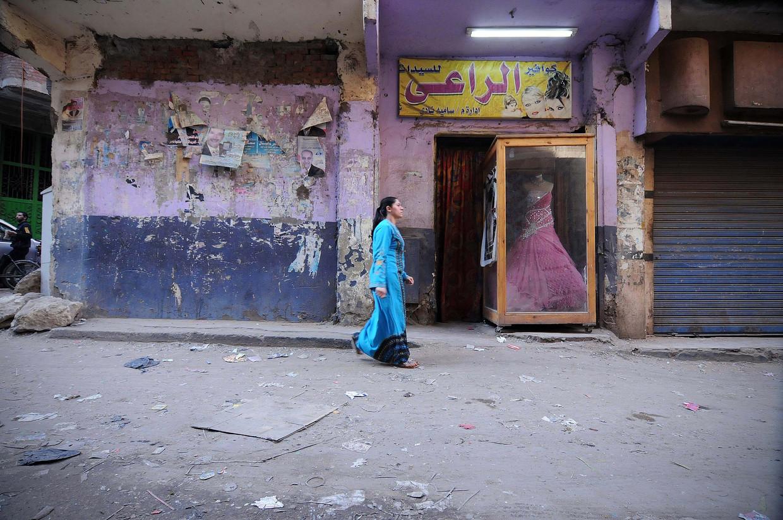 Een vrouw wandelt langs een bruidswinkel in Manshiyat Naser, het armste deel van Cairo. Arme meisjes worden jong uitgehuwelijkt.