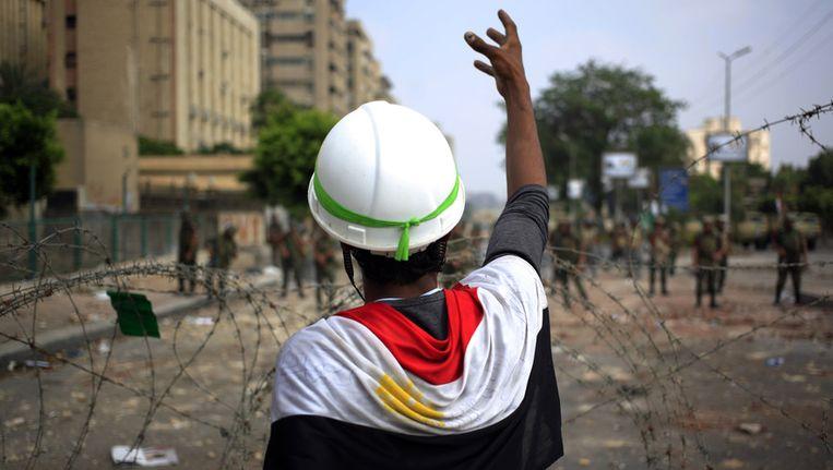 Een aanhanger van Mursi maakt gebaren richting Egyptische soldaten die het hoofdkwartier van de Republikeinse Garde in Caïro bewaken. Beeld AP