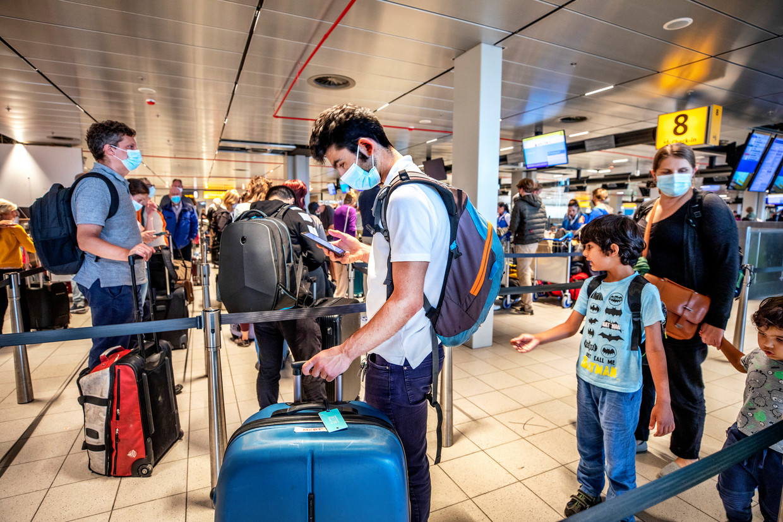 Op Schiphol moeten passagiers hun corona-app laten zien bij het inchecken. Beeld Raymond Rutting/VK