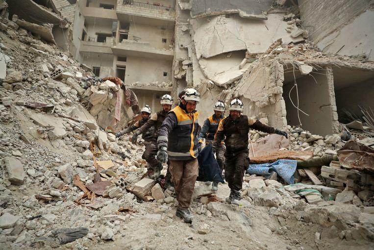 Reddingswerkers dragen een lichaam weg tussen het puin van gebouwen in Ariha, in de Syrische provincie Idlib. Beeld AFP