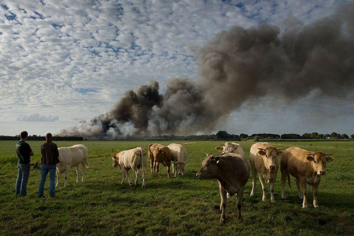 Brand bij varkenshouderij Knorhof, boeren uit de omgeving kijken toe.