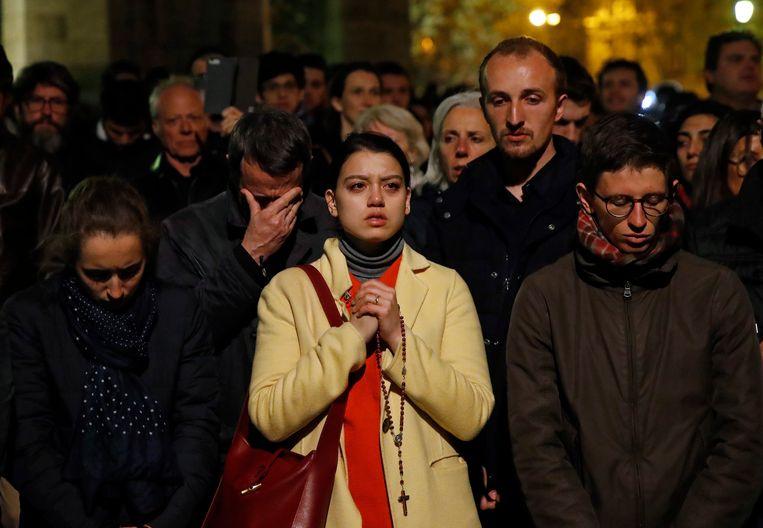 Biddende mensen terwijl de Notre-Dame door vlammen verteerd wordt. Beeld AP