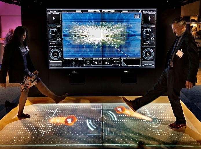 Twee bezoekers van de Precisiebeurs schoppen tegen 'protonen' op de stand van Cern.