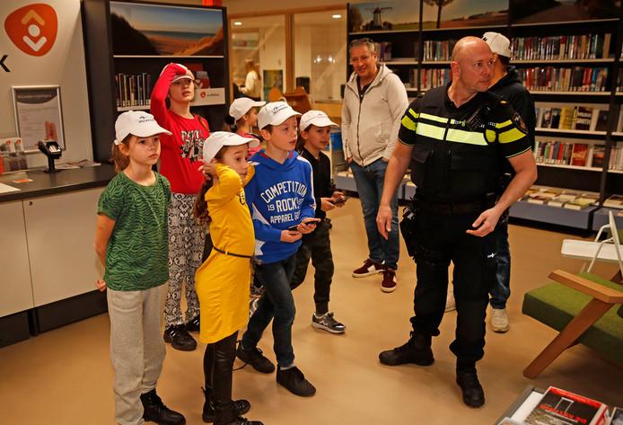 Kinderen en de wijkagent overleggen waar ze moeten zoeken naar de zakkenroller tijdens de workshop 'Pak de boef!'.