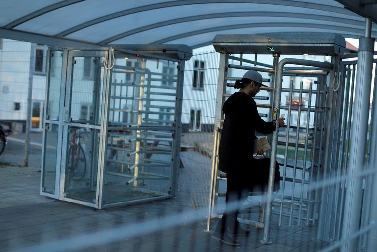 Een Koerdische Irakees gaat een uitzetcentrum voor afgewezen asielzoekers binnen in het Deense Jutland. Beeld REUTERS