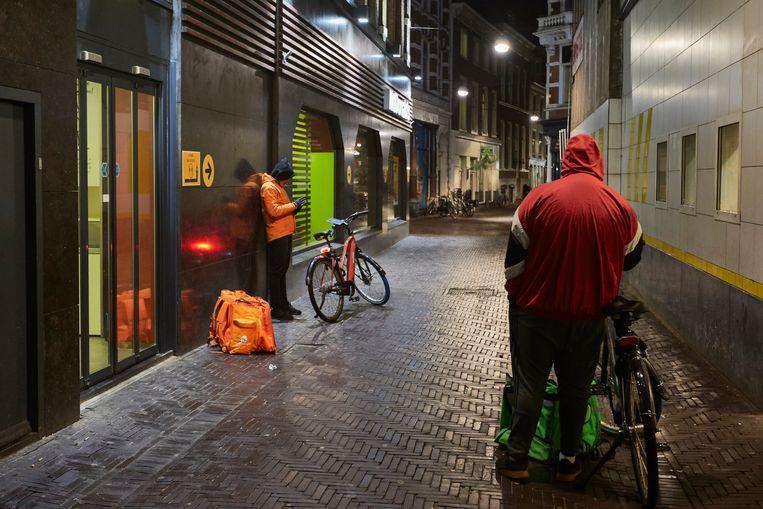 Voedselbezorgers in afwachting van een te bezorgen maaltijd in Den Haag. Beeld Getty Images