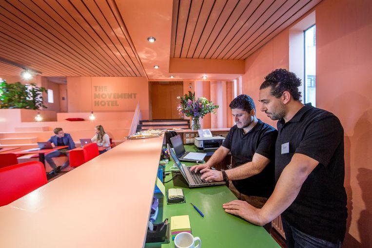 Op de foto links: Khaled werkzaam als frontdesk manager. Beeld Jean-Pierre Jans