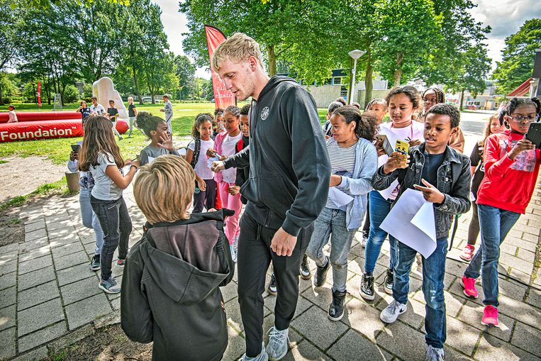Donny van de Beek wordt bestormd door leerlingen.  Beeld Guus Dubbelman / de Volkskrant