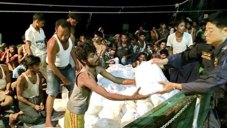 A Royal Thai Navy handout photo made available on 19 May 2015 shows some 450 ethnic Rohingya migrants believed to be from Myanmar and Bangladesh on a boat, which was abandoned by it's captain and crew, receiving food, water and other aid supplies from Thai navy officers in the Andaman Sea, near Lipe island, Satun province, close to the Malaysian border. Beeld EPA