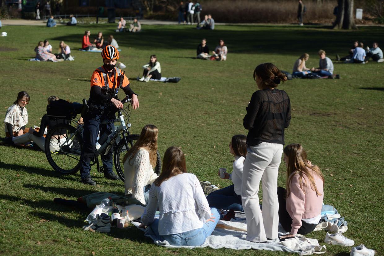 Een agent controleert de social distancing in het Leuvense stadspark. Jongeren kwamen er – net als op andere plaatsen – de voorbije dagen massaal samen om even te ontsnappen aan de lockdown.  Beeld Vertommen