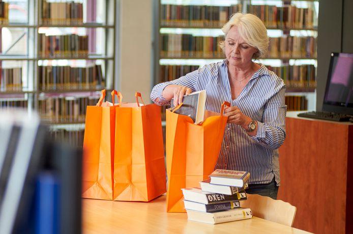 Willeke Pijnenburg is bezig met het samenstellen van een verrassingstas in de bibliotheek in Oss.