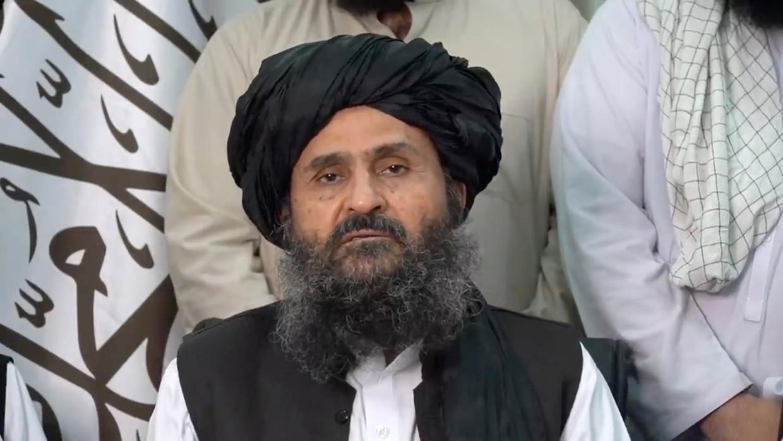 Mullah Abdul Ghani Baradar zat centraal tijdens een videoboodschap waarin de taliban opnieuw de controle over het land opeist. Beeld Via REUTERS