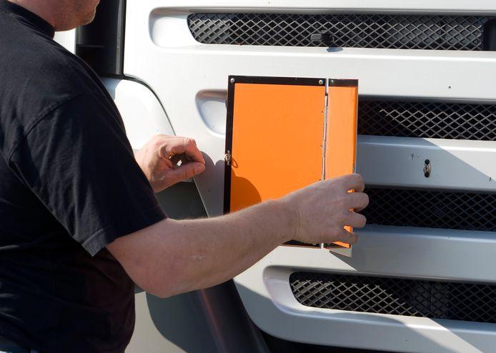 Een vrachtwagenchauffeur bevestigt aan de voorzijde een oranje bord wat aangeeft dat hij  gevaarlijke stoffen transporteert.
