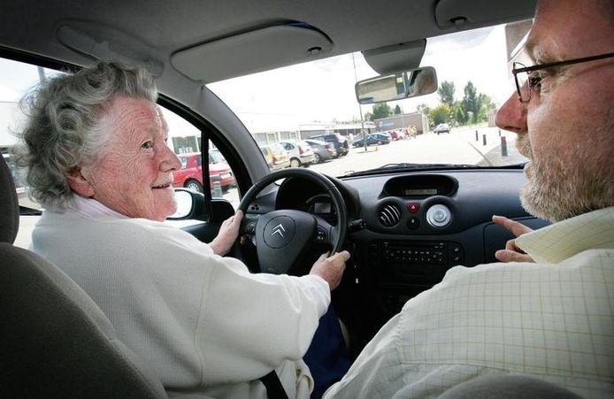Vera Teulings (85) maakt een rit door Den Bosch onder toeziend oog van rij-instructeur Jan Cools. Foto Sandra Peerenboom