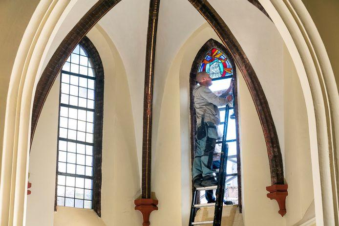 Een medewerker van het bedrijf Van der Staaij bezig met de plaatsing van de nieuwe glas-in-loodramen.