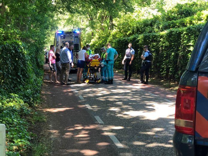 Omstanders en ambulancepersoneel ontfermen zich over het slachtoffer.