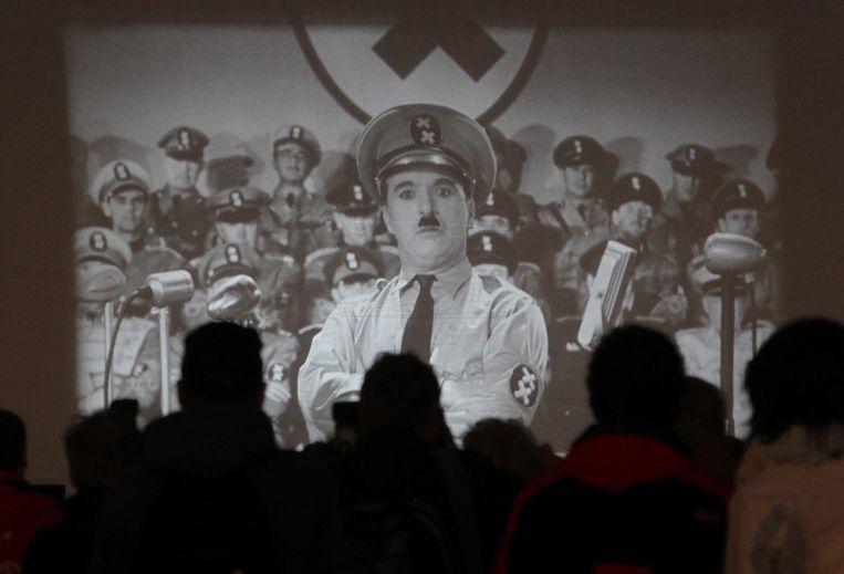 Mensen kijken vanaf het Parizer Platz in Berlijn naar een vertoning van The Great Dictator van Charlie Chaplin Beeld epa