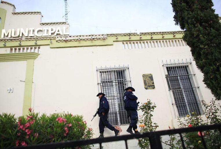 Politieagenten patrouilleren bij het stadhuis van de plaats La Tuna na de arrestatie van drugsbaas Joaquin 'El Chapo' Guzmán, twee weken geleden. Beeld reuters