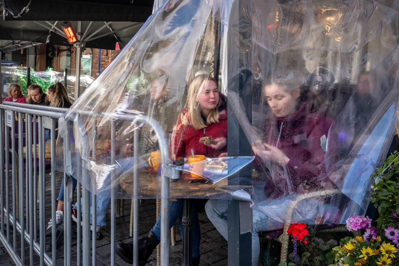 Achter dranghekken en onder plastic lunchen op het terras van café De Druif op de Bossche Markt.