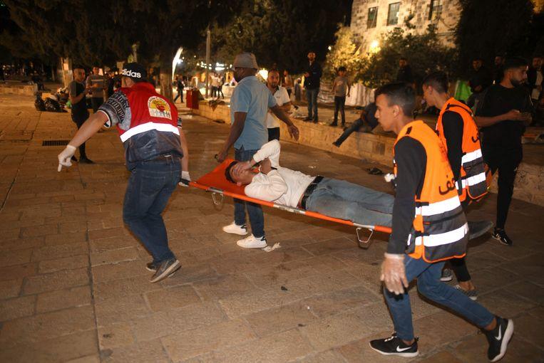 Een gewonde man wordt weggedragen terwijl Israëlische veiligheidsdiensten botsen met Palestijdense demonstranten bij de   de Al-Aqsa-moskee in Jeruzalem. (07/05/2021) Beeld AFP