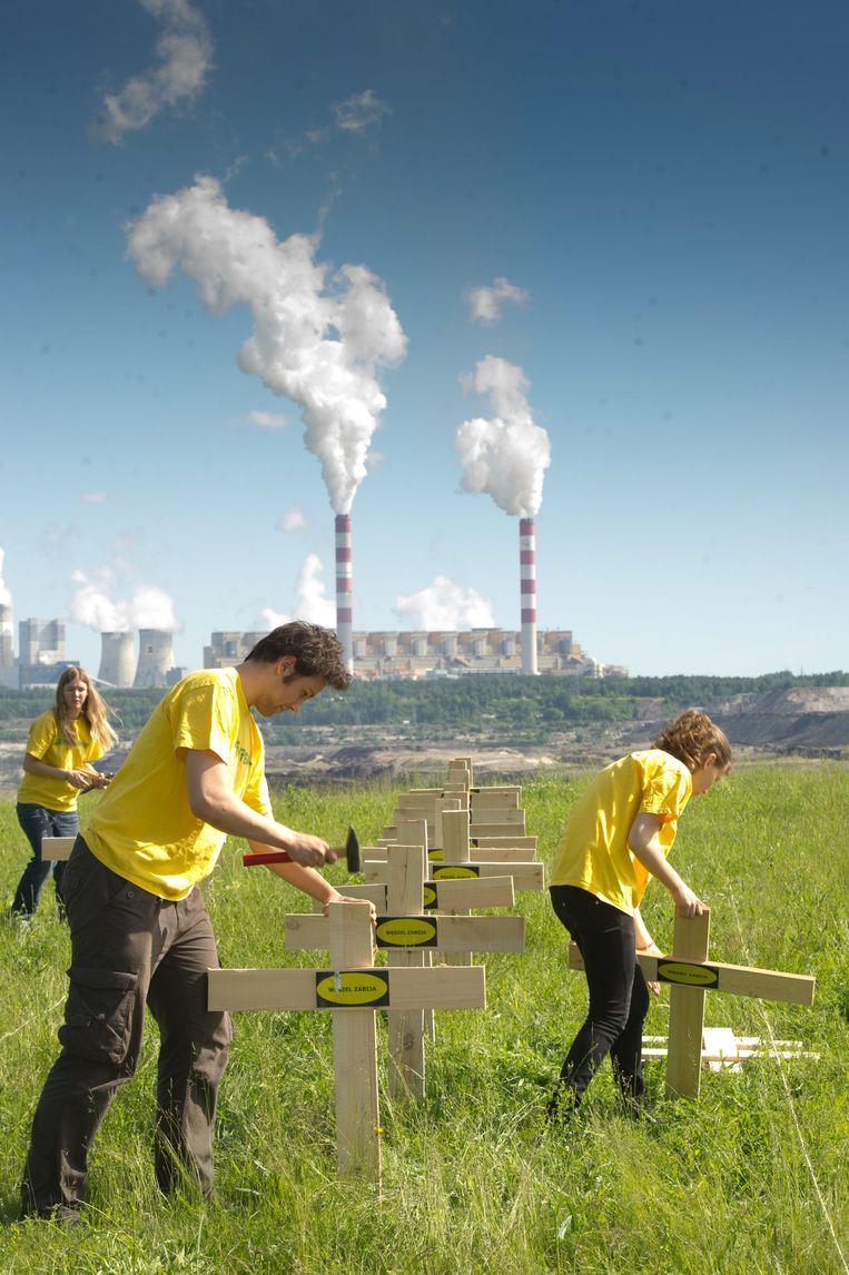 Greenpeace-activisten zetten kruisen neer met de inscriptie 'kool doodt' nabij de energiecentrale in Belchatow in Polen. Beeld EPA