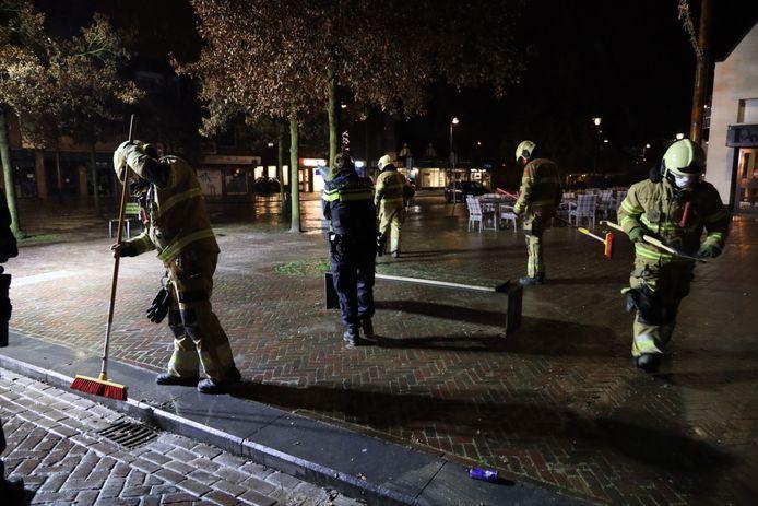 Brandweer ruimt het glas van de brandbom op.