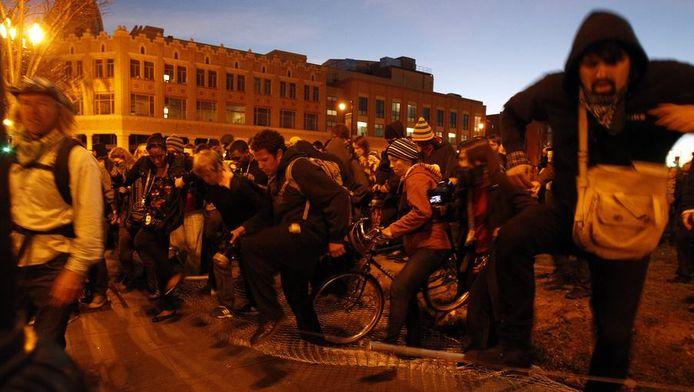 Occupy-betogers in Oakland lopen over een hek om arrestatie te voorkomen, 28 januari.
