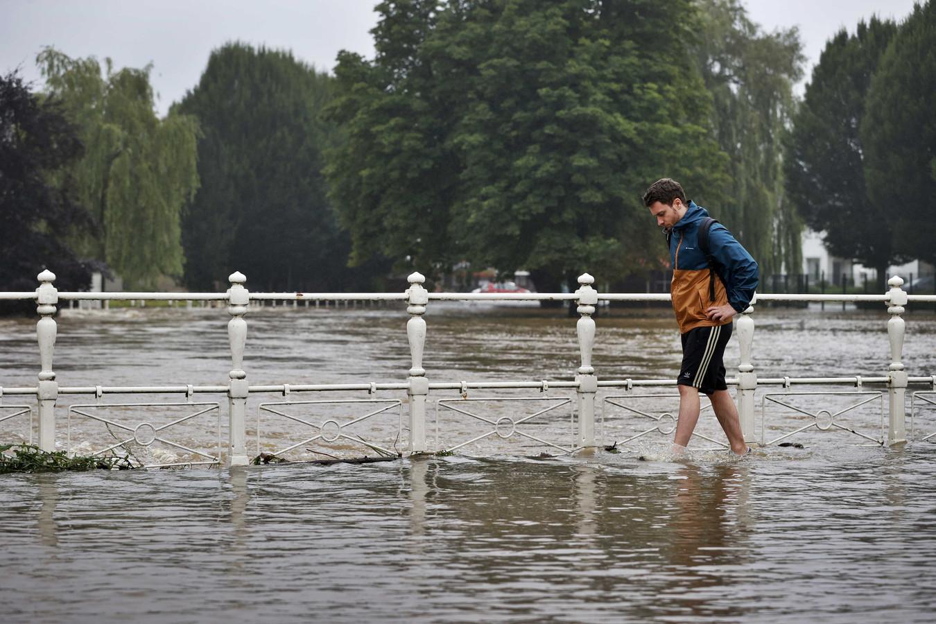 Een passant loopt door het water in Zuid-Limburg.