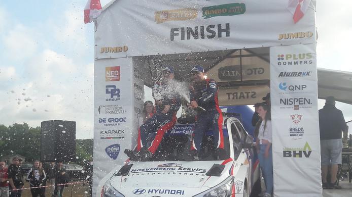 Bob de Jong (rechts) en zijn navigator Bjorn Degandt spuiten de champagne in het rond na het winnen van de GTC Rally.