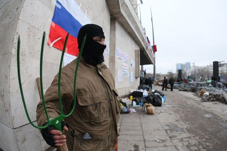 Een pro-Russische betoger met hooivork houdt de wacht voor het bezette bestuursgebouw in Donetsk. Beeld AFP