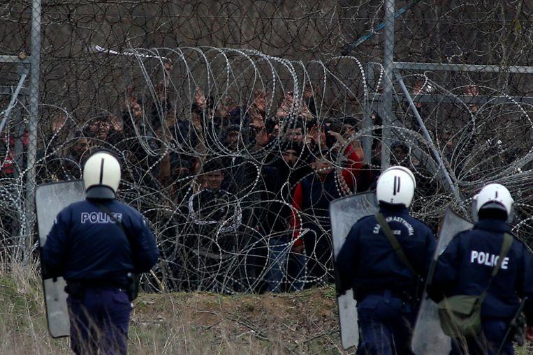 Griekse oproerpolitie staat aan de grens met Turkije op 4 maart dit jaar om migranten die willen oversteken tegen te houden.  Beeld AP/Giannis Papanikos
