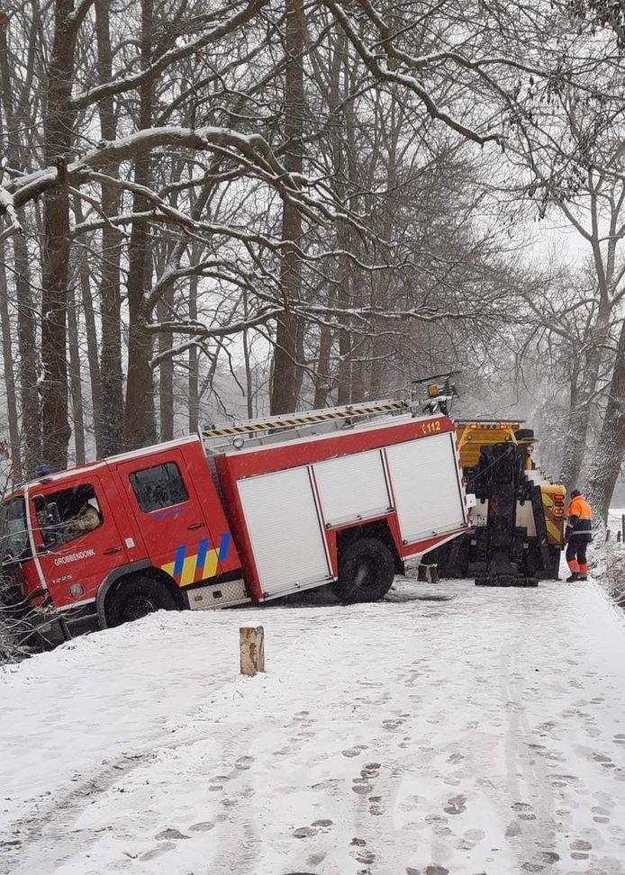 De brandweerwagen moest uit de gracht getakeld worden.