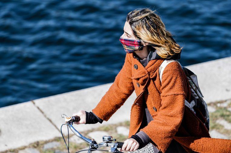 Een fietser probeert zich te beschermen tegen het virus met een mondkapje. Beeld Photo News
