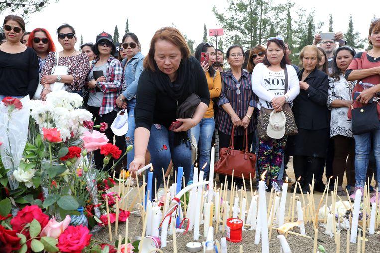 Vrouwen leggen bloemen neer en steken kaarsen aan ter nagedachtenis aan de slachtoffers. Beeld EPA