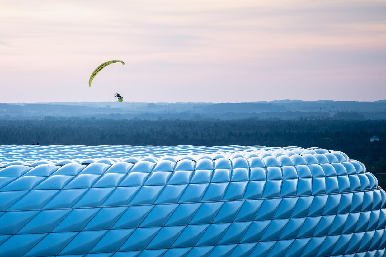 De Greenpeace-activist boven de Allianz Arena in München, voordat hij een kabel raakte. Beeld DPA